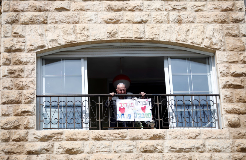 """Elias Feinzilberg, a 102-year-old Holocaust survivor, stands at the window of his home in Jerusalem as Israel marks Holocaust Remembrance Day under coronavirus disease (COVID-19) restrictions, April 21, 2020. The Hebrew words on the placard read: """"Remembering close-by, embracing from afar."""" (photo credit: RONEN ZVULUN/REUTERS)"""
