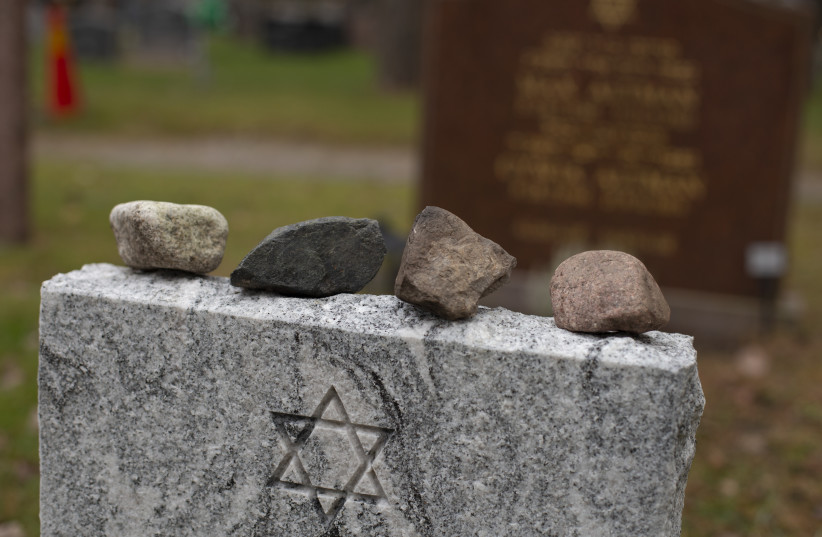 Placing stones on a headstone at a Jewish cemetery marks the memory of and honors the deceased. (photo credit: GETTY IMAGES)