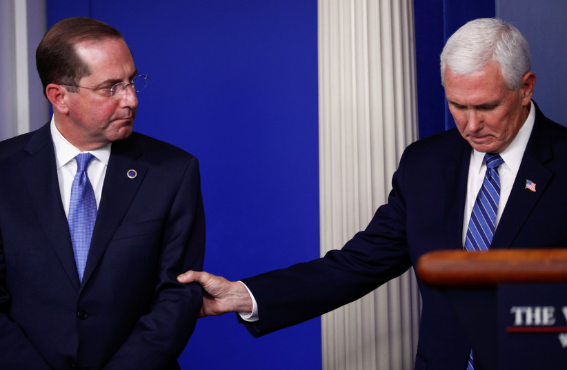 US Vice President Pence reaches out and grabs the arm of HHS Secretary Azar during daily coronavirus response briefing at the White House in Washington (photo credit: REUTERS/TOM BRENNER)