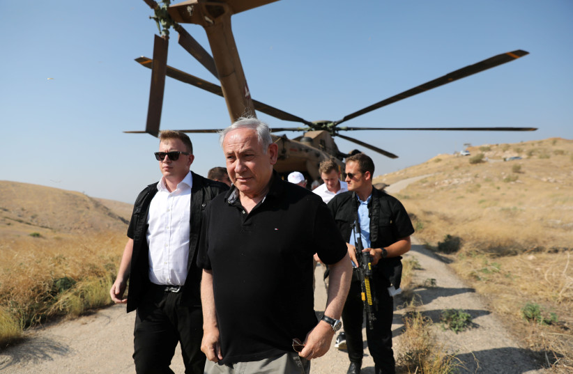 PRIME MINISTER Benjamin Netanyahu walks out of a military helicopter, as he visits an old army outpost overlooking the Jordan Valley last year. (photo credit: ABIR SULTAN / REUTERS)