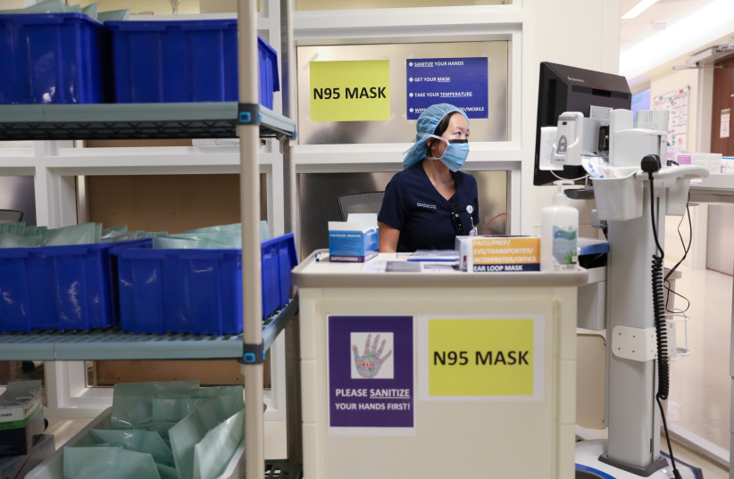 A member of medical staff wearing a protective face mask, works at an N95 face mask collection point, amid the coronavirus disease (COVID-19) outbreak, at the Cleveland Clinic hospital in Abu Dhabi, United Arab Emirates, April 20, 2020 (photo credit: REUTERS/CHRISTOPHER PIKE)