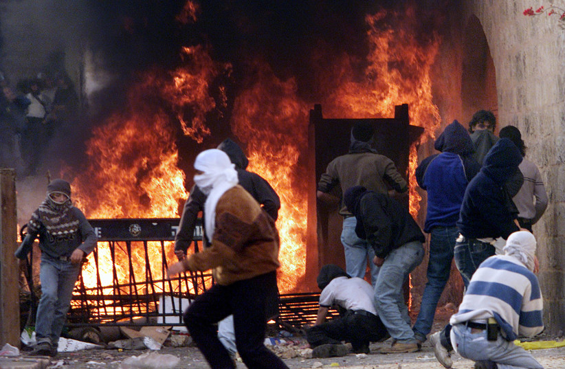 Palestinians man a burning barricade on the Via Dolorosa in Jerusalem's Old City as they fight violent clashes with Israeli Border Police, December 2000 (photo credit: REUTERS)