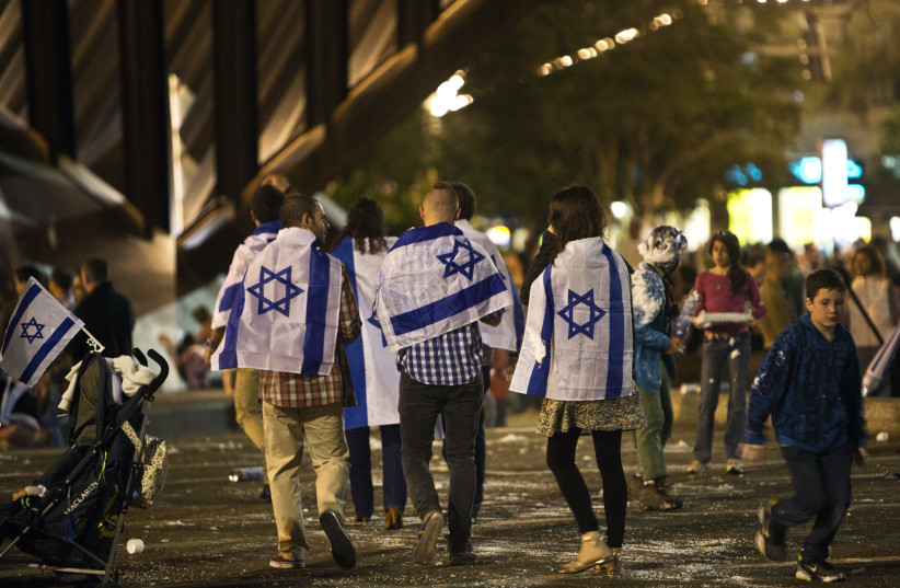 People covered with Israeli national flags walk onto Rabin square to take part in the celebrations for Israel's Independence Day at its 65th anniversary of the creation of the state in Tel Aviv (photo credit: NIR ELIAS / REUTERS)