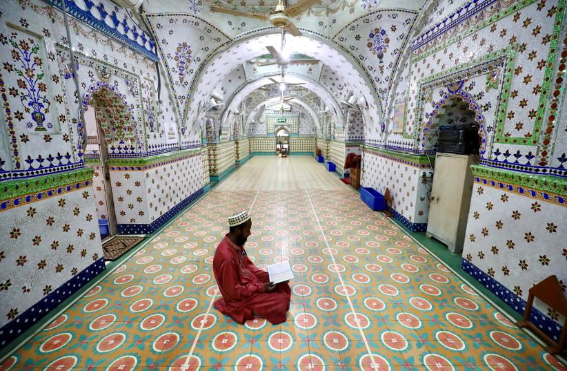 A Muslim devotee recites the Koran at the Star Mosque during Ramadan in Dhaka, Bangladesh, April 26, 2020 (photo credit: REUTERS/MOHAMMAD PONIR HOSSAIN)