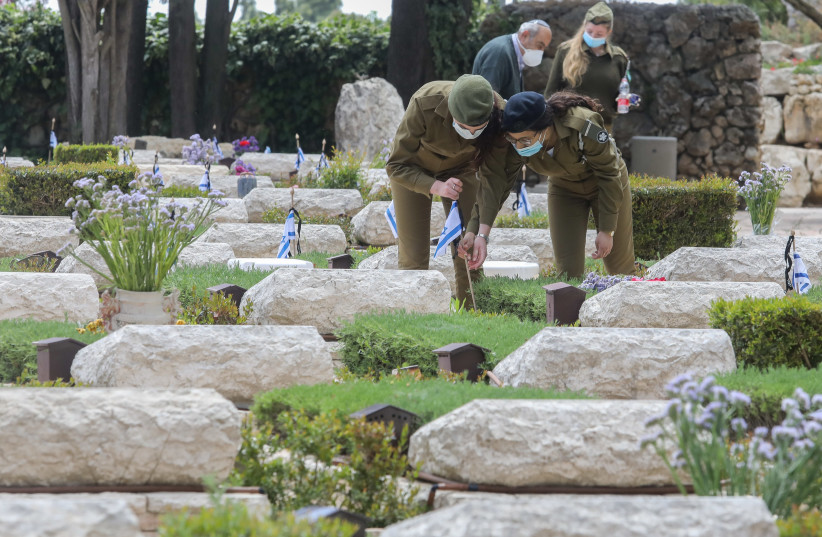 IDF soldiers place Israeli flags on the graves of fallen soldiers at Mount Hertzl ahead of Israel's Memorial Day (photo credit: MARC ISRAEL SELLEM/THE JERUSALEM POST)