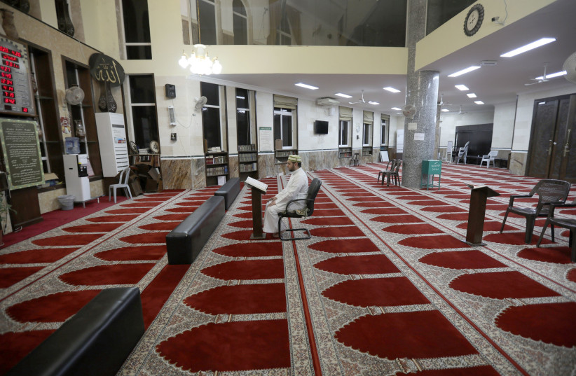 A Jordanian Imam reads the Koran in an empty mosque during Ramadan as prayers by worshipers are suspended due to concerns about the spread of the coronavirus. Amman, Jordan, April 26, 2020. (photo credit: MOHAMMAD HAMED / REUTERS)