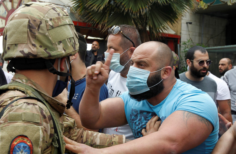 A Lebanese demonstrator gestures to a Lebanese soldier, during a protest against the collapsing Lebanese pound currency and the price hikes, in Zouk, north of Beirut (photo credit: REUTERS/MOHAMED AZAKIR)