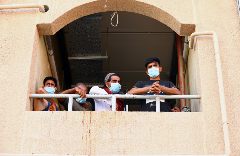 Workers wear masks during the outbreak of the coronavirus disease (COVID-19) in Dubai, United Arab Emirates April 23, 2020 (photo credit: REUTERS)