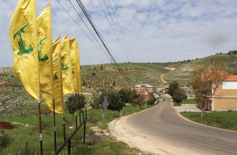 HEZBOLLAH FLAGS flutter along an empty street, at the entrance of Mays Al-Jabal village (photo credit: SETH J. FRANTZMAN)