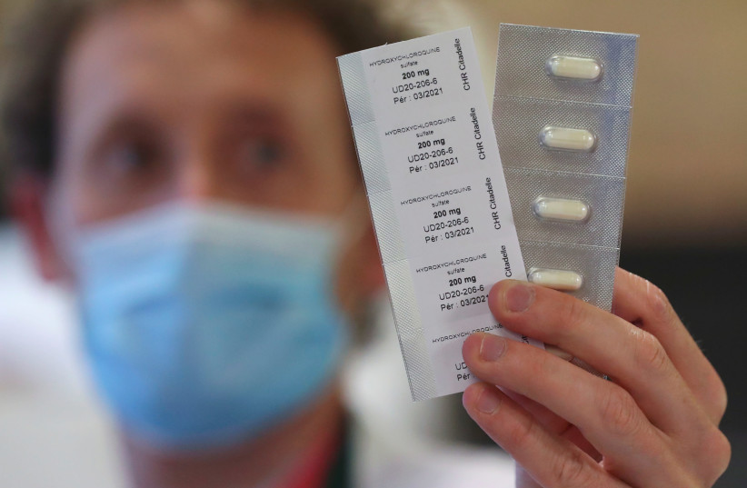 A pharmacy worker shows pills of hydroxychloroquine used to treat the coronavirus disease (COVID-19) at the CHR Centre Hospitalier Regional de la Citadelle Hospital in Liege, Belgium, April 22, 2020. (photo credit: YVES HERMAN / REUTERS)