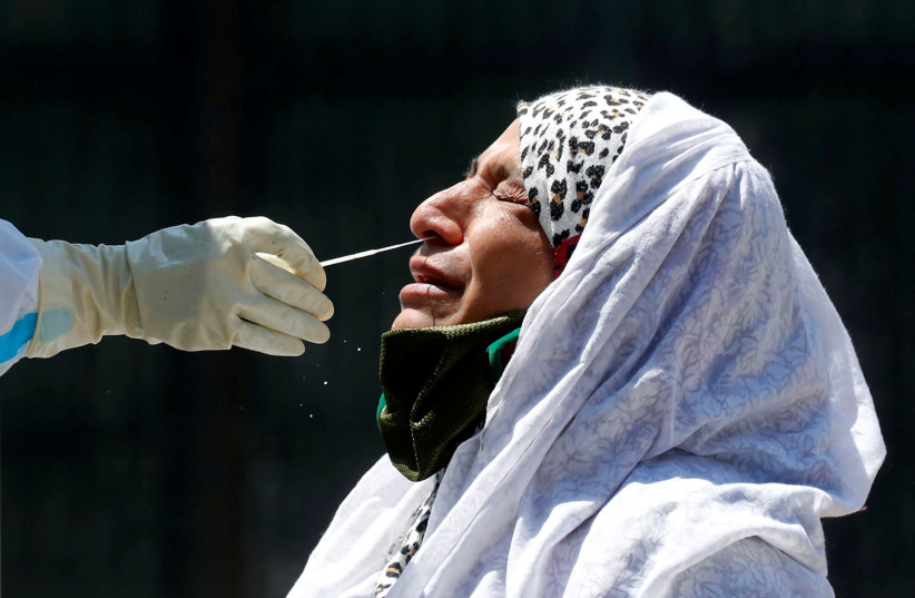 A woman reacts as a doctor wearing a protective glove takes a swab to test for coronavirus disease (COVID-19) at a residential area in Srinagar (photo credit: REUTERS/DANISH ISMAIL)