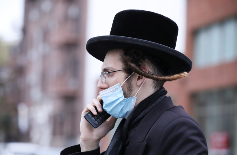 An Orthodox Jewish man wears a mask while talking on a cellphone in the Orthodox Jewish community of the Borough Park neighborhood during the outbreak of the coronavirus disease (COVID19) in the Brooklyn borough of New York, U.S., April 30, 2020. (photo credit: REUTERS/CAITLIN OCHS)