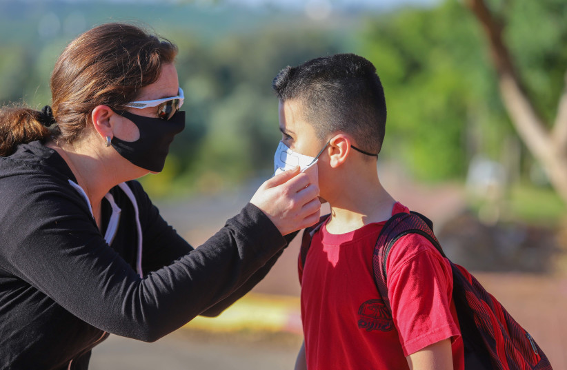 Israeli children wearing face masks make their way to school in Moshav Yashresh, on May 3, 2020 (photo credit: YOSSI ALONI/FLASH90)
