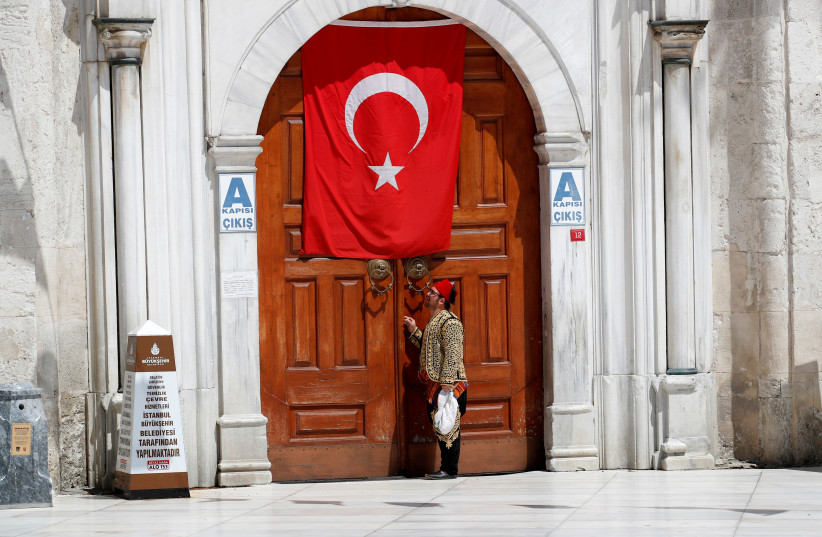 A man stands in fron of closed Eyup Sultan Mosque during the first day of Ramadan and the second of a four-day curfew, as the spread of the coronavirus disease (COVID-19) continues, in Istanbul, Turkey April 24, 2020 (photo credit: UMIT BEKTAS / REUTERS)