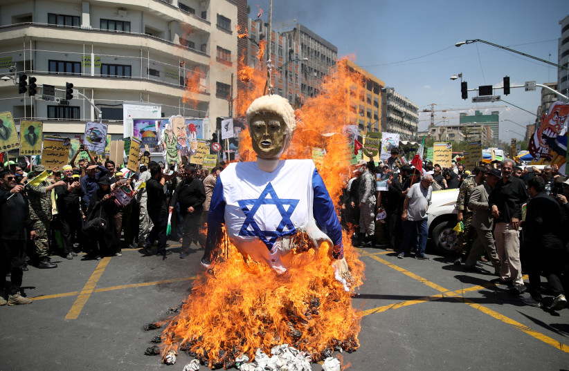 Iranians burn an effigy in the likeness of U.S. President Donald Trump during a protest marking the annual al-Quds Day (Jerusalem Day) on the last Friday of the holy month of Ramadan in Tehran, Iran June 8, 2018 (photo credit: TASNIM NEWS AGENCY)