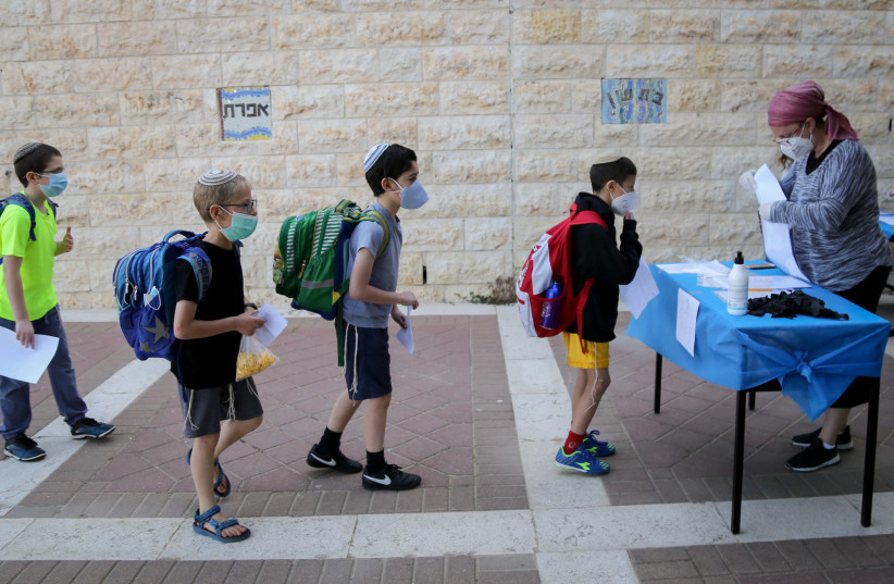 Israeli students at the Orot Etzion school in Efrat wear protective face masks as they return to school for the first time since the outbreak of the coronavirus, May 3, 2020 (photo credit: GERSHON ELINSON/FLASH90)