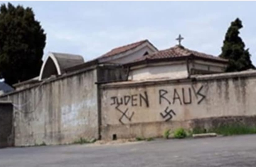Antisemitic graffiti is seen outside a cemetary in Soveria Mannelli, Italy. (photo credit: LACNEWS24)
