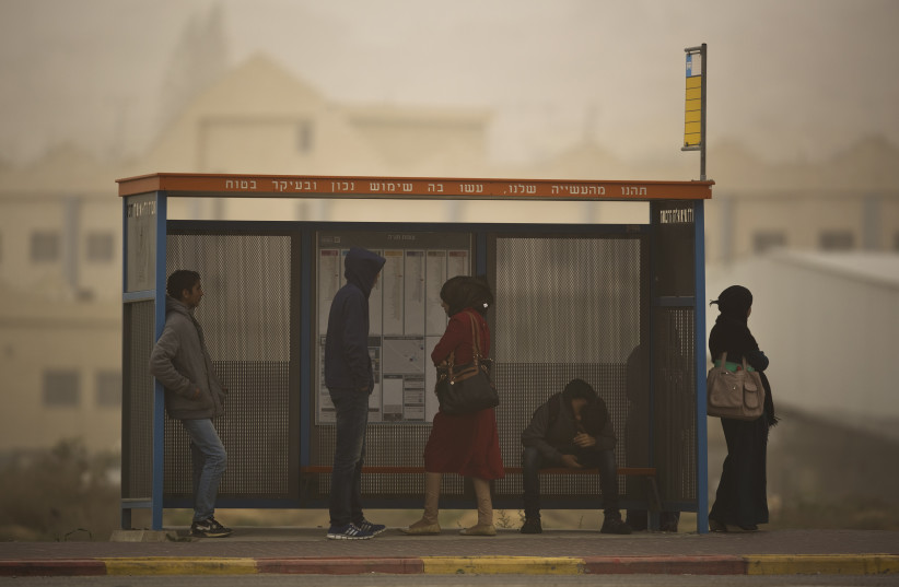 Bedouins wait at a bus stop during a sandstorm in the southern Bedouin city of Hura (photo credit: REUTERS/AMIR COHEN)