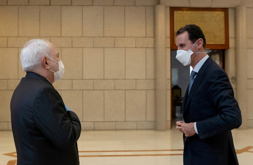 Syria's President Bashar al-Assad and Iran's Foreign Minister Mohammad Javad Zarif, wearing face masks as protection against the spread of the coronavirus disease (COVID-19), meet in Damascus, Syria, in this handout released by SANA on April 20, 2020 (photo credit: SANA/HANDOUT VIA REUTERS)