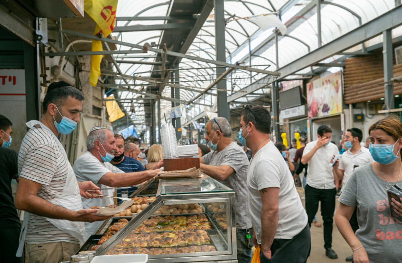 Israelis wear face masks for fear of the coronavirus as they walk through the market in Ramle on May 1, 2020. Daily Isaraeli life is slowly getting back after the outbreak of the Coronavirus. (photo credit: YOSSI ALONI/FLASH90)