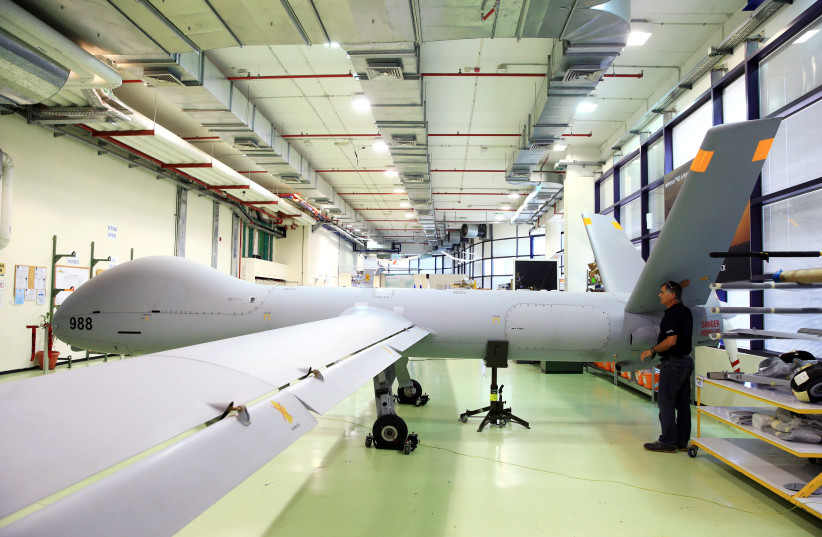 An employee stands next to an Elbit Systems Ltd. Hermes 900 unmanned aerial vehicle (UAV) at the company's drone factory in Rehovot, Israel (photo credit: REUTERS/OREL COHEN)