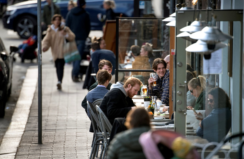 SWEDES ENJOY themselves at an outdoor restaurant amid the coronavirus outbreak, in Stockholm on April 20 (photo credit: REUTERS)