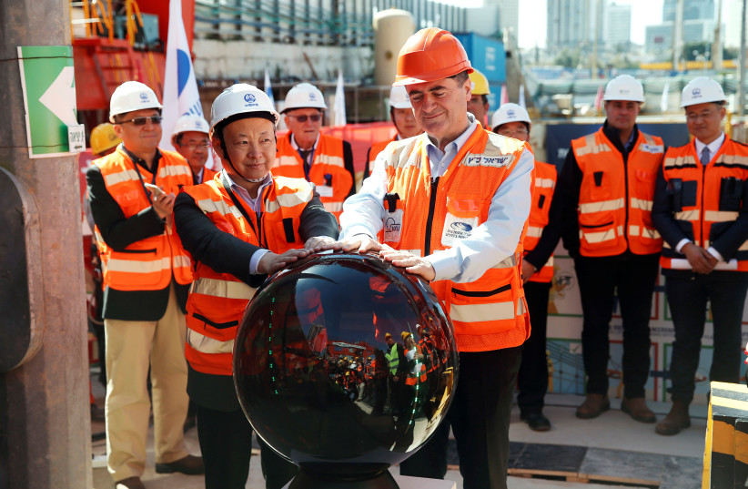 Israel Katz (front), Israel's then-minister of transport, and employees of China Railway Engineering Corporation, take part in an event marking the beginning of underground construction work of the light rail, using a Tunnel Boring Machine (TBM), in Tel Aviv, Israel February 19, 2017 (photo credit: REUTERS/BAZ RATNER)