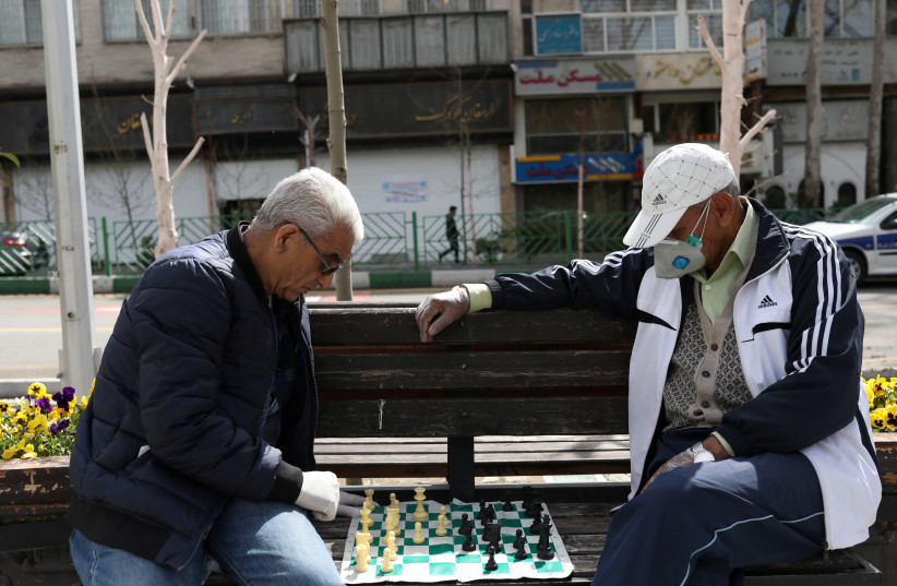 Men wear protective face masks and gloves, amid fear of coronavirus disease (COVID-19), play chess on the sidewalk of Mellat Park, in Tehran, Iran (photo credit: REUTERS)