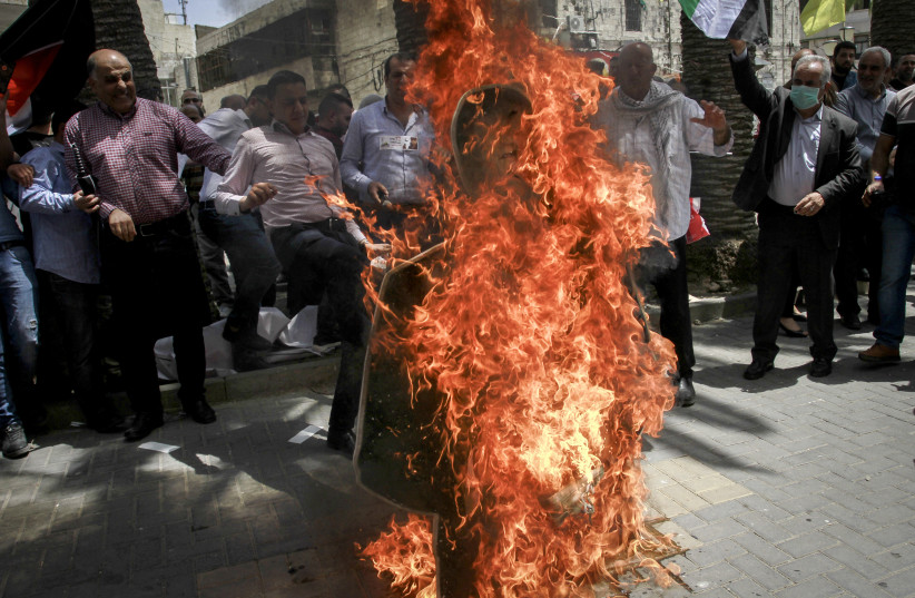 Palestinian protestors burn a Photo of US Secretary of State Mike Pompeo, during a protest against U.S. President Donald Trump's Middle East peace plan, in the West Bank city of Nablus, May 14, 2020. (photo credit: NASSER ISHTAYEH/FLASH90)