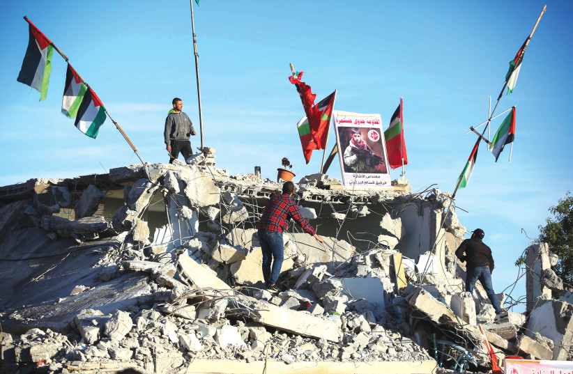 AFTER THE IDF demolished it, Palestinians stand on the remains of the house of Qassam Al-Barghouti who was involved in the murder of 17-year-old Rina Shnerb, last year. (photo credit: FLASH90)