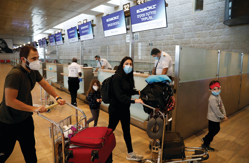 PASSENGERS WEARING masks push trolleys yesterday at the departures terminal at Ben-Gurion Airport. (photo credit: RONEN ZVULUN / REUTERS)