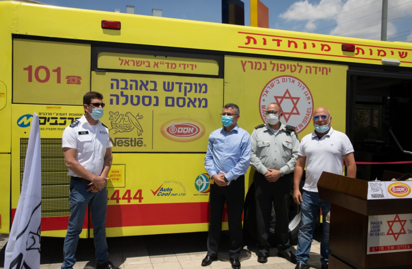 Magen David Adom staff and IDF officers standing in front of the newly built ambulance-bus (photo credit: Courtesy)