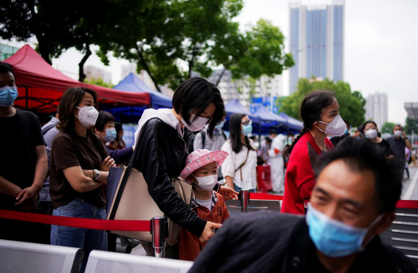 Residents wearing face masks queue for nucleic acid testings in Wuhan, the Chinese city hit hardest by the coronavirus disease (COVID-19) outbreak, Hubei province, China May 16, 2020 (photo credit: REUTERS/ALY SONG)