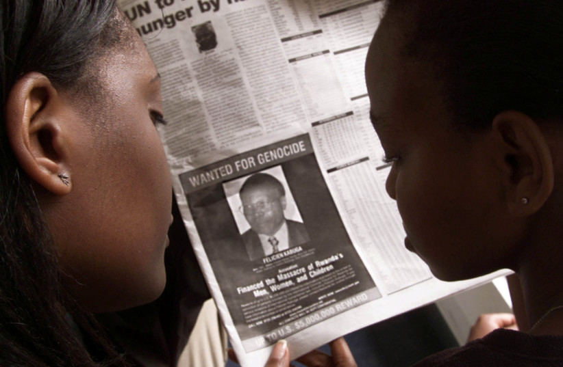 "Readers look at a newspaper June 12, 2002 in Nairobi carrying the photograph of Rwandan Felicien Kabuga wanted by the United States. The United States published a ""wanted"" photograph in Kenyan newspapers of the businessman accused of helping finance the 1994 killings in Rwanda. (photo credit: REUTERS/GEORGE MULALA/FILE PHOTO)"