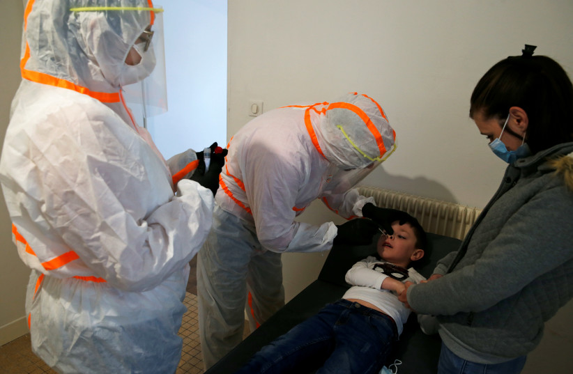 A French doctor, wearing a protective suit and a face mask, administers a nasal swab to a 6-year-old child during a COVID-19 testing in Gouzeaucourt, during the outbreak of the coronavirus disease (COVID-19) in France, May 16, 2020. (photo credit: PASCAL ROSSIGNOL/REUTERS)