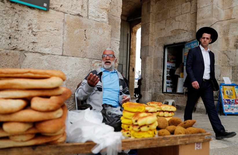 An orthodox Jewish man walks next to a vendor at one of the entrances to Jerusalem's Old City March 9, 2020 (photo credit: RONEN ZVULUN/REUTERS)