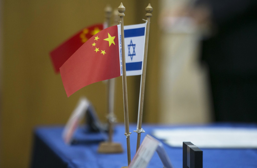 Chinese and Israeli flags are seen on a table during a signing ceremony in Tel Aviv, 2014 (photo credit: BAZ RATNER/REUTERS)