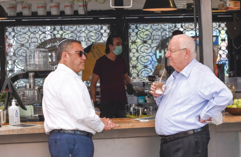 PRESIDENT REUVEN RIVLIN enjoys a takeaway iced coffee while visiting the Jerusalem Business Center with Jerusalem Mayor Moshe Lion. (photo credit: NOAM MORANO)