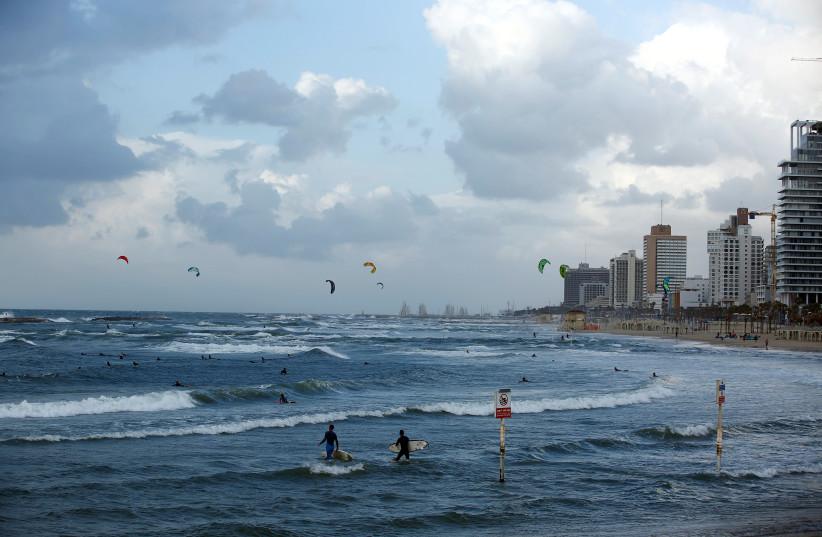 Surfers walk into the water of the Mediterranean Sea (photo credit: REUTERS/CORINNA KERN)