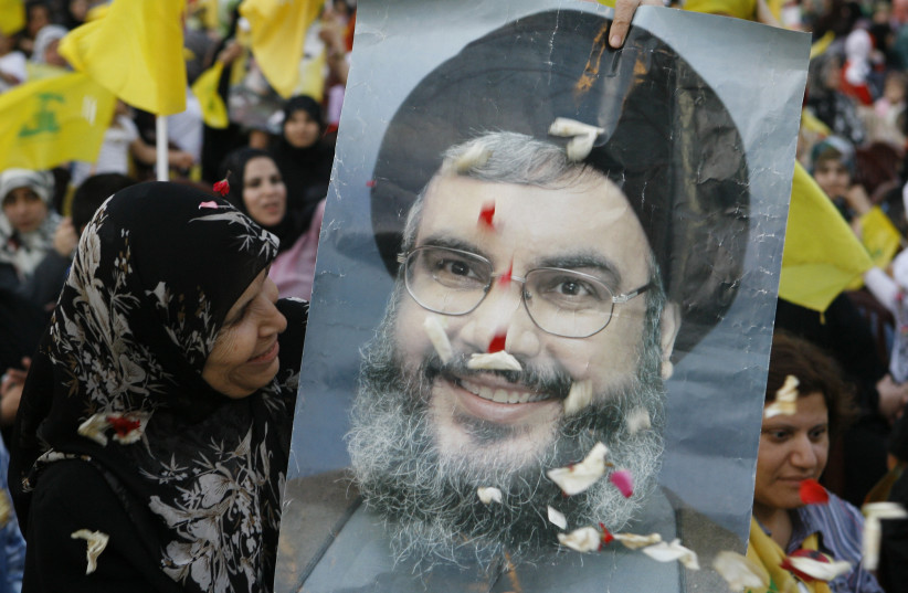 A HEZBOLLAH supporter beams at a poster of Hezbollah leader Hassan Nasrallah during a rally on the anniversary of the Israeli withdrawal, on May 25, 2009 (photo credit: JAMAL SAIDI/ REUTERS)