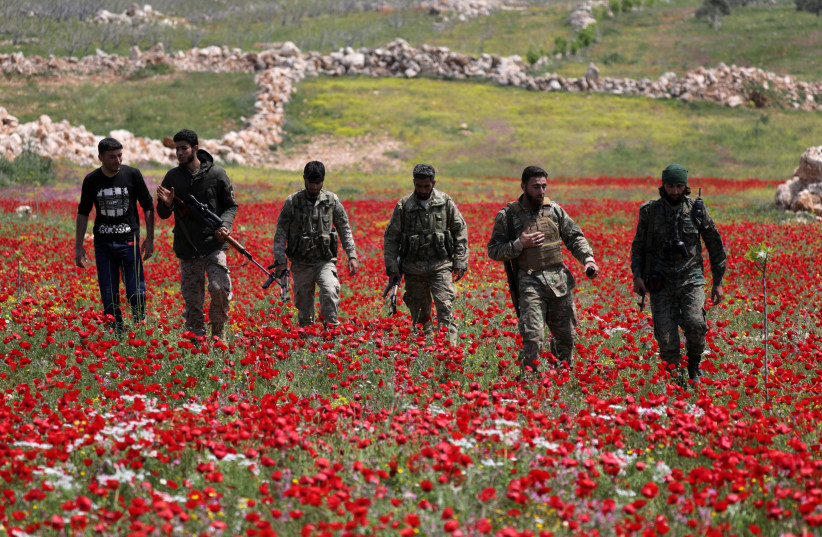TURKEY-BACKED Syrian rebel fighters walk through a field of flowers in Idlib's southern countryside, in Syria in April (photo credit: KHALIL ASHAWI / REUTERS)