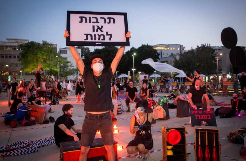 Street performers take part in a protest calling for financial support from the Israeli government at Habima Square in Tel Aviv, following the lockdown Israel has been in order to prvevent the spread of the Coronavirus, on May 20, 2020. (photo credit: MIRIAM ALSTER/FLASH90)