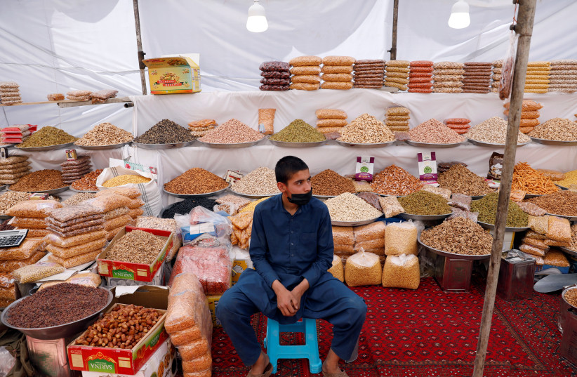 An Afghan boy waits for customers ahead of the Eid al-Fitr, marking the end of the fasting month of Ramadan amid the spread of the coronavirus disease (COVID-19), in Kabul, Afghanistan May 21, 2020 (photo credit: REUTERS/MOHAMMAD ISMAIL)
