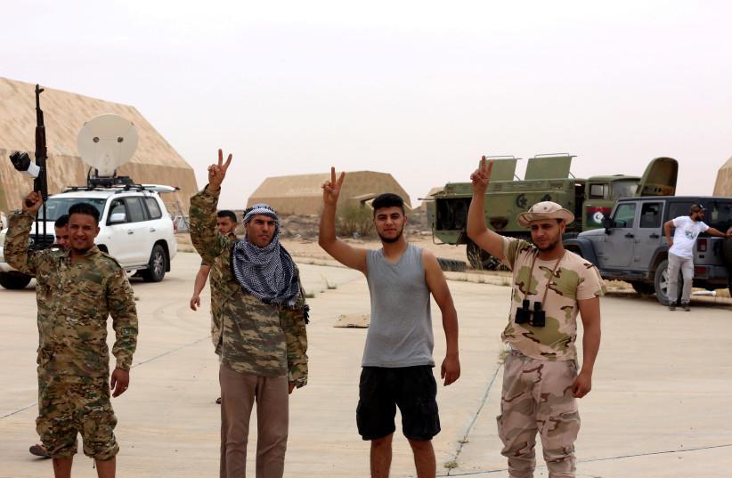 Des membres du gouvernement libyen internationalement reconnu affichent des signes de victoire après avoir pris le contrôle de la base aérienne de Watiya, au sud-ouest de Tripoli, en Libye, le 18 mai 2020. (crédit photo: REUTERS / HAZEM AHMED)
