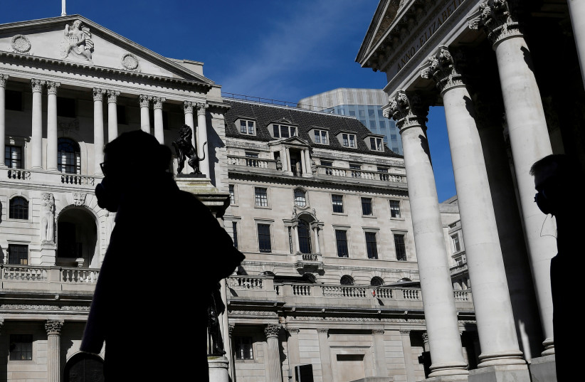 People wearing masks walk past the Bank of England (photo credit: REUTERS)