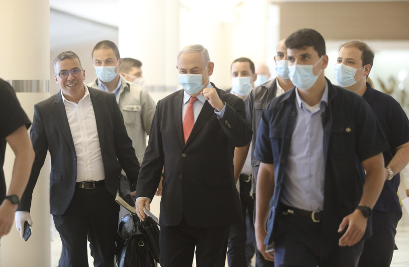 Prime Minister Benjamin Netanyahu walking through the Knesset, wearing a mask amid the coronavirus pandemic (photo credit: MARC ISRAEL SELLEM/THE JERUSALEM POST)