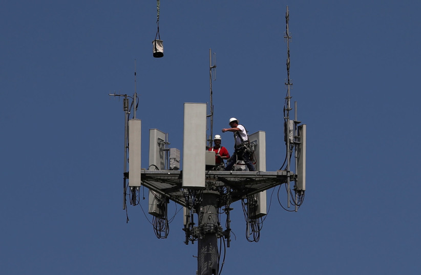 Workers install 5G telecommunications equipment on a T-Mobile tower in Seabrook, Texas. May 6, 2020 (photo credit: REUTERS/ADREES LATIF)