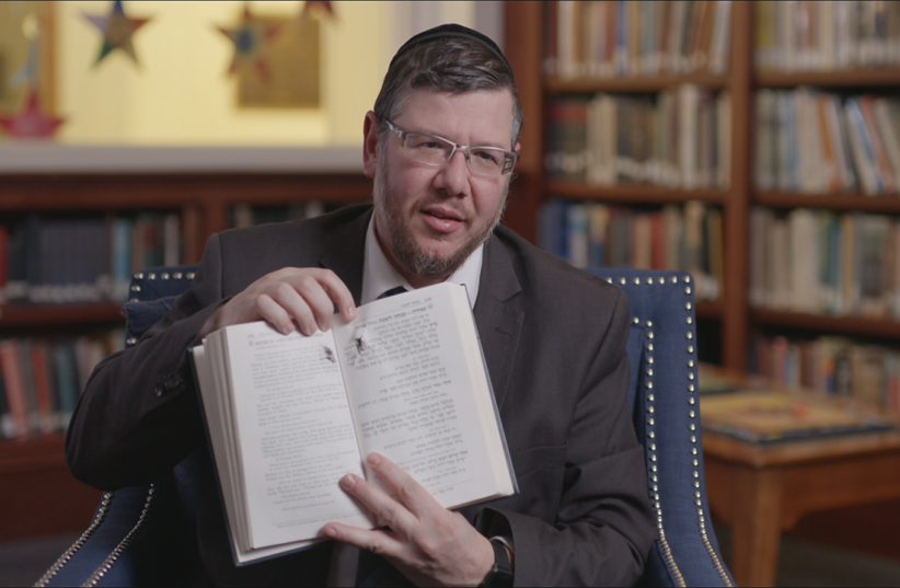 "In ""Viral: Antisemitism in Four Mutations,"" Rabbi Elisar Admon shows the hole where a bullet pierced his prayer book during the Tree of Life Synagogue shooting in Pittsburgh. ""It went right through the word for God,"" he said. (photo credit: PBS/JTA)"