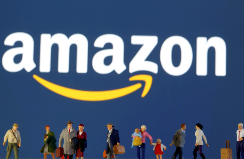 Small toy figures are seen in front of diplayed Amazon logo (photo credit: REUTERS/ DADO RUVIC)