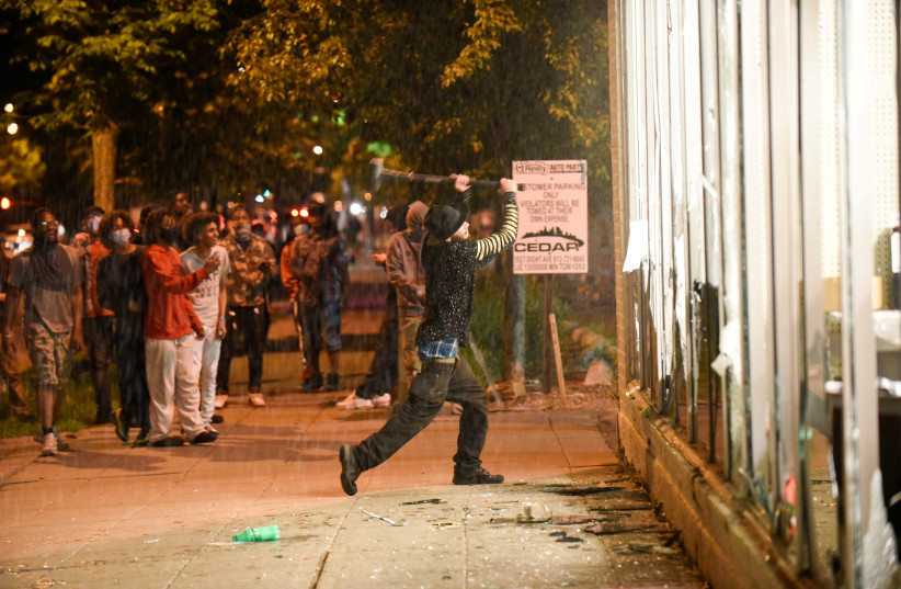 A protester vandalizes an O'Reilly's near the Minneapolis Police third precinct, where demonstrators gathered after a white police officer was caught on a bystander's video pressing his knee into the neck of African-American man George Floyd, who later died at a hospital, in Minneapolis (photo credit: REUTERS/NICHOLAS PFOSI)
